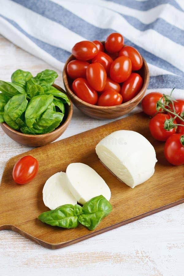 Τυρί μοτσαρελών με τις κόκκινα ντομάτες και τα φύλλα βασιλικού, πιπέρι, ελαιόλαδο στοκ φωτογραφία