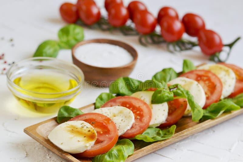 Τυρί μοτσαρελών με τις κόκκινα ντομάτες και τα φύλλα βασιλικού στοκ εικόνες με δικαίωμα ελεύθερης χρήσης