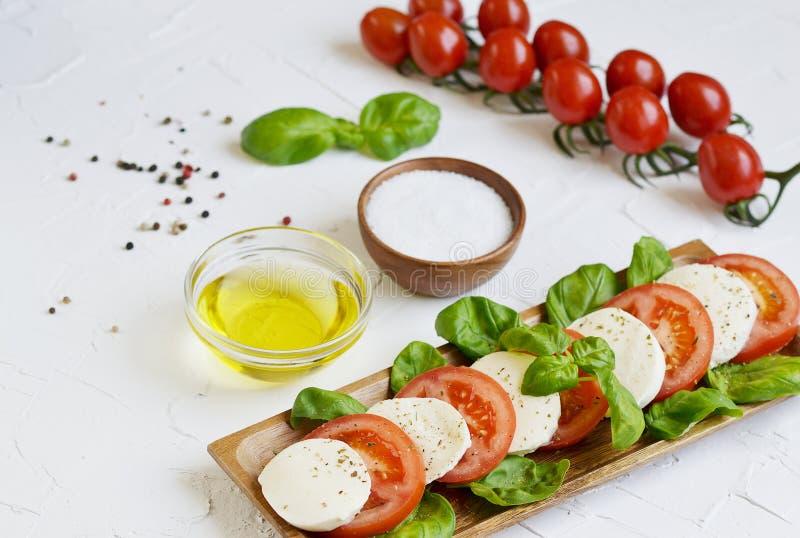 Τυρί μοτσαρελών με τις κόκκινα ντομάτες και τα φύλλα βασιλικού στοκ εικόνα με δικαίωμα ελεύθερης χρήσης