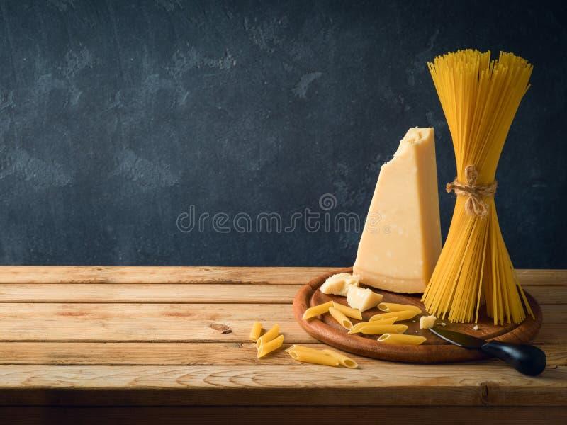 Τυρί παρμεζάνας, μακαρόνια και ζυμαρικά στον ξύλινο πίνακα στοκ εικόνα