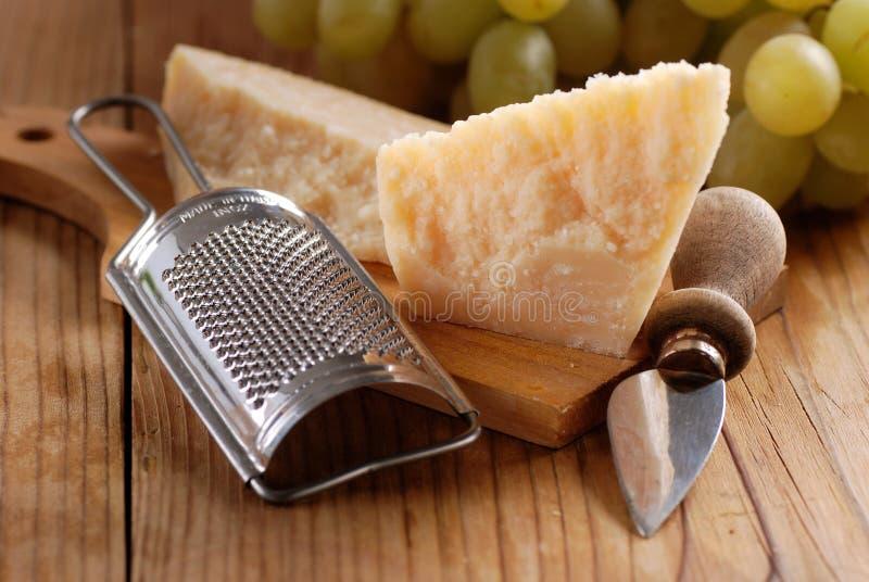 Τυρί παρμεζάνας στον τέμνοντα πίνακα στοκ εικόνες