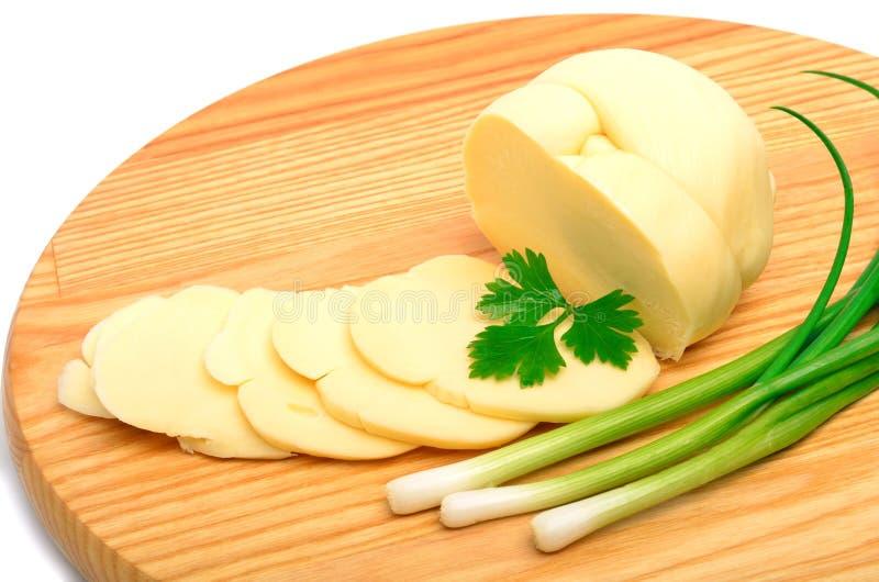 Τυρί, φέτες τυριών και πράσινο κρεμμύδι στον ξύλινο πίνακα στοκ φωτογραφία