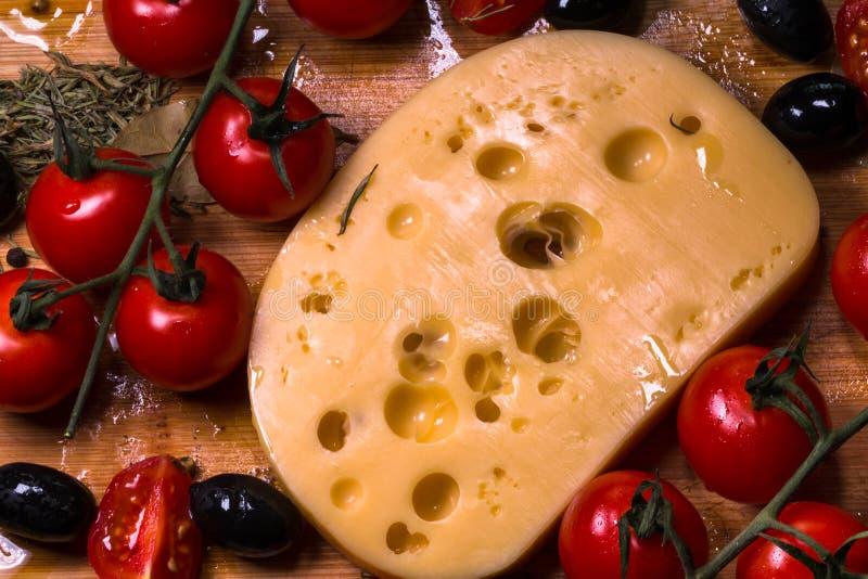 Τυρί Emmental με τις ντομάτες και βασιλικός στο ξύλο στοκ εικόνες