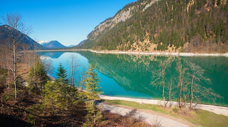 Τυρκουάζ ήρεμη τεχνητή λίμνη sylvenstein στην πρόωρη άνοιξη στοκ φωτογραφία