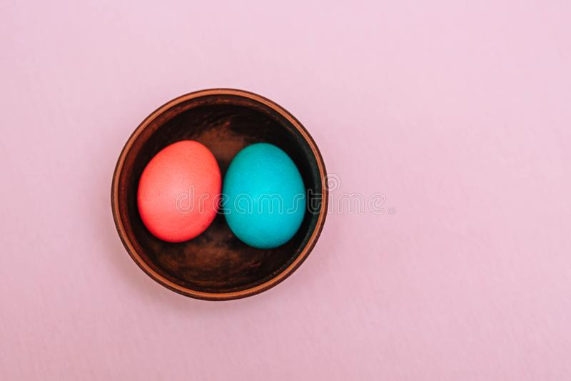 Τυρκουάζ και ρόδινα αυγά Πάσχας σε ένα ξύλινο πιάτο σε ένα ρόδινο υπόβαθρο r στοκ φωτογραφίες