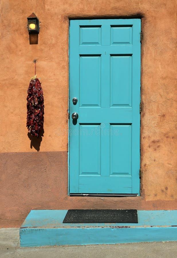 Τυρκουάζ ξύλινη πόρτα ένα ristra τσίλι και ένας τοίχος πλίθας στοκ φωτογραφίες με δικαίωμα ελεύθερης χρήσης