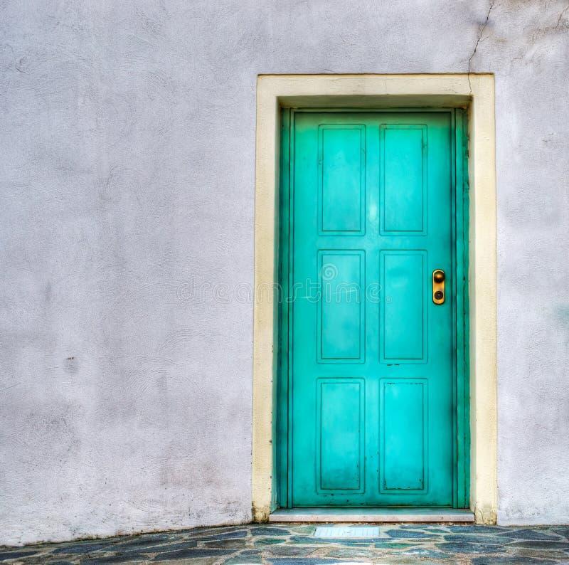 Τυρκουάζ πόρτα σε έναν γκρίζο τοίχο στοκ εικόνες