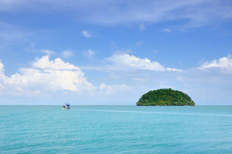 Τυρκουάζ τροπική θάλασσα με το αλιευτικό σκάφος και μικρό νησί στον ορίζοντα κάτω από το μπλε ουρανό με τα φυσικά σύννεφα στο Koh στοκ φωτογραφία με δικαίωμα ελεύθερης χρήσης