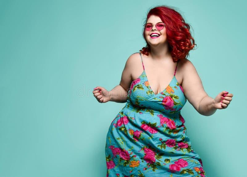 Τυχερή γυναικεία υπέρβαρη γυναίκα συν-μεγέθους στα γυαλιά ηλίου μόδας και το ζωηρόχρωμο ευτυχή χορό sundress, εορτασμός στοκ φωτογραφίες