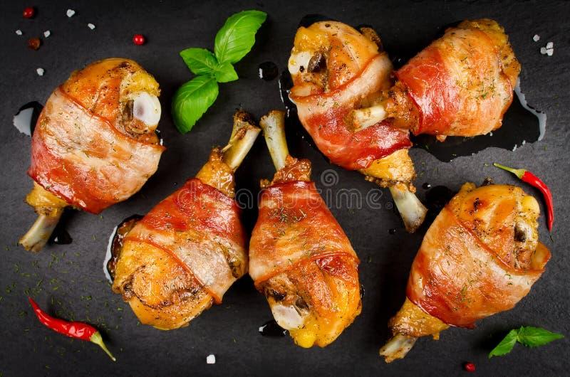 Τυλιγμένα μπέϊκον πόδια κοτόπουλου σε ένα μαύρο υπόβαθρο στοκ φωτογραφία με δικαίωμα ελεύθερης χρήσης