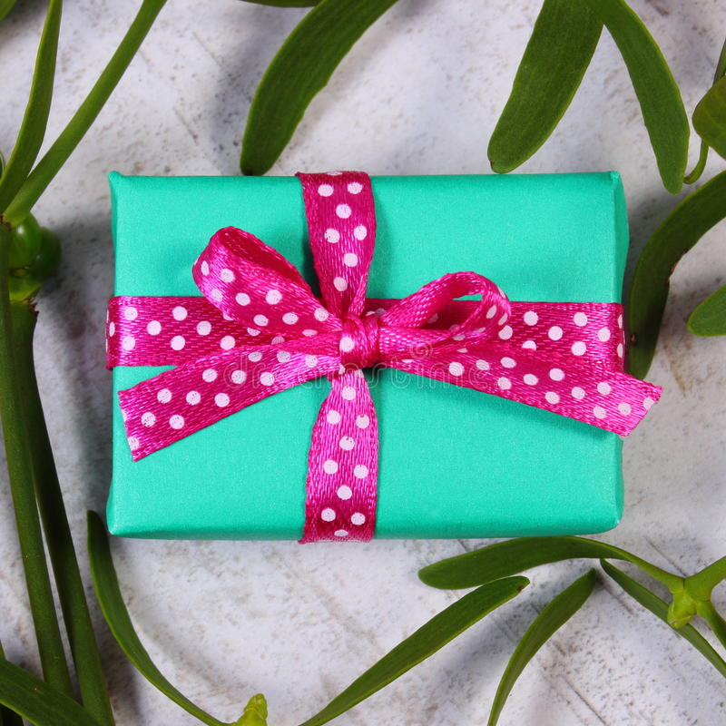 Τυλιγμένο πράσινο δώρο για τα Χριστούγεννα και γκι στο παλαιό ξύλινο υπόβαθρο στοκ φωτογραφίες με δικαίωμα ελεύθερης χρήσης