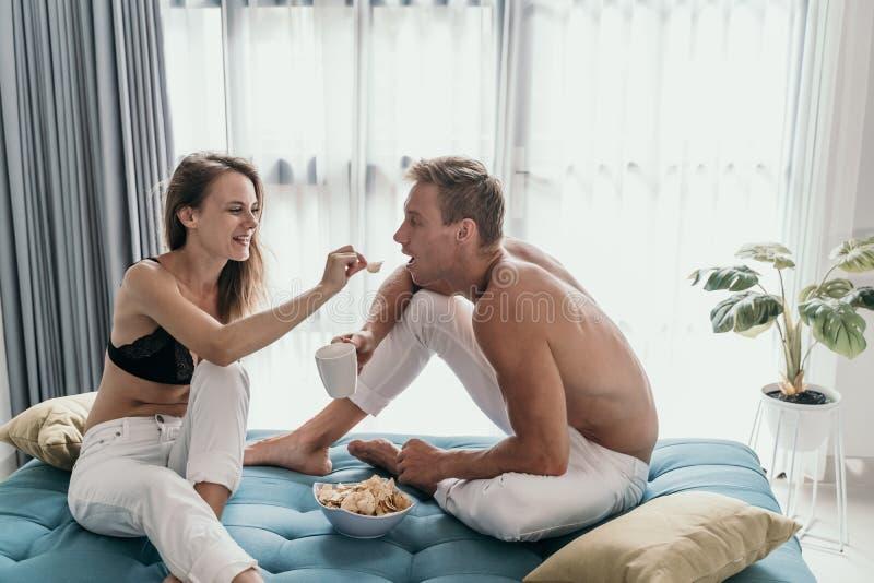 Τόπλες ζεύγος που έχει τη διασκέδαση που τρώει το πρόχειρο φαγητό στοκ εικόνα με δικαίωμα ελεύθερης χρήσης