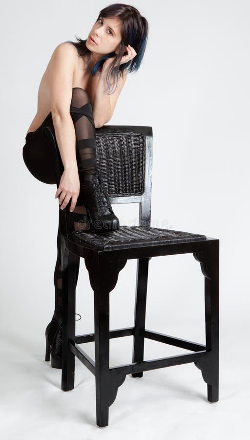 Τόπλες γυναίκα στις αποκόπτως περικνημίδες που κλίνουν στην έδρα στοκ εικόνες
