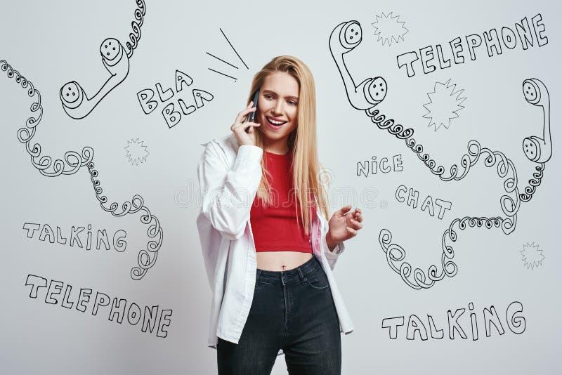 Τόσο ευτυχής να σας ακούσει! Έκπληκτη ξανθή νέα γυναίκα που μιλά στο έξυπνο τηλέφωνο και που αισθάνεται τόσο ευτυχής στεμένος ενά στοκ εικόνες