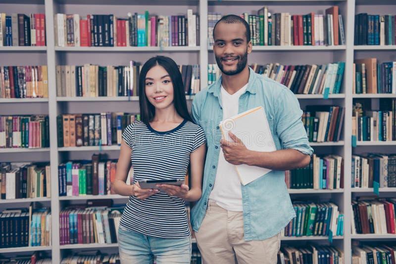 Τόσο καλός! Το ζεύγος των διεθνών σπουδαστών είναι στη βιβλιοθήκη τ στοκ φωτογραφία