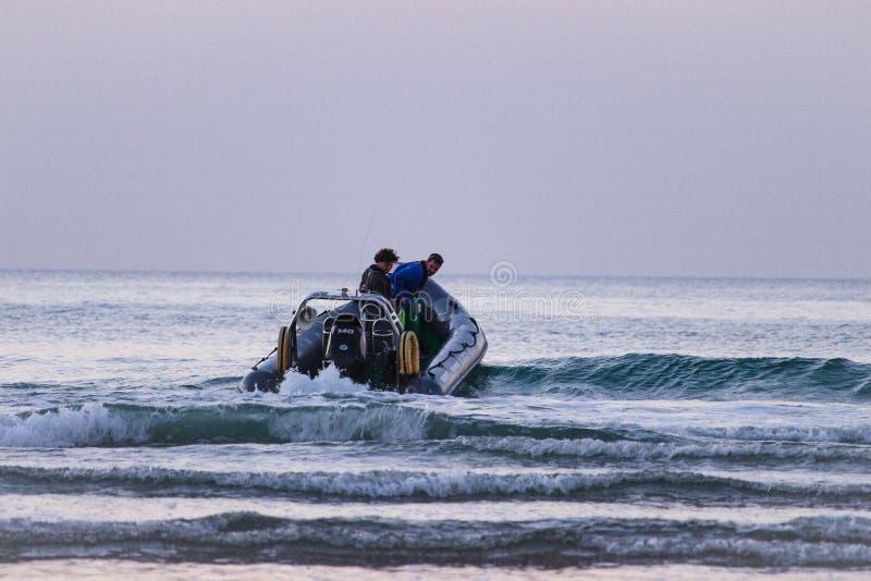 2 τύποι που έχουν τη διασκέδαση με τους βάρκα στα κύματα στοκ φωτογραφίες με δικαίωμα ελεύθερης χρήσης
