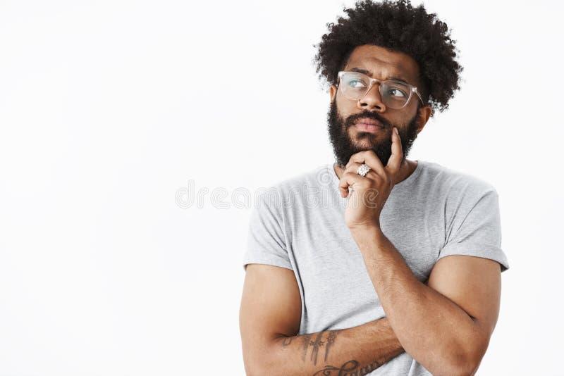 Τύπος αφροαμερικάνων στα γυαλιά που κάνουν το σχέδιο στο μυαλό που σκέφτεται επάνω το χέρι εκμετάλλευσης καταλόγων παντοπωλείων σ στοκ εικόνα