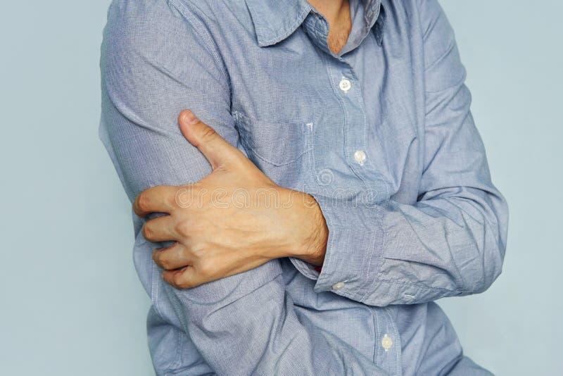 τύπος με στο χέρι εκμετάλλευσης πουκάμισων ενός άρρωστου bicep Ο πόνος στο βραχίονά μου Επώδυνοι δικέφαλοι μυ'ες ένα κίνητρο αρθρ στοκ φωτογραφίες με δικαίωμα ελεύθερης χρήσης
