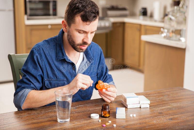 Τύπος που βάζει τα χάπια σε ένα κιβώτιο στο σπίτι στοκ φωτογραφία με δικαίωμα ελεύθερης χρήσης