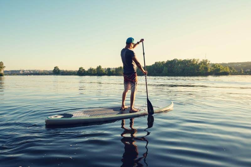 Τύπος που κωπηλατεί σε έναν πίνακα ΓΟΥΛΙΑΣ στο μεγάλο ποταμό στοκ φωτογραφίες με δικαίωμα ελεύθερης χρήσης