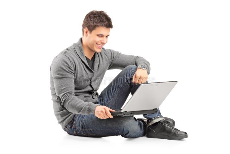 Τύπος που λειτουργεί σε ένα lap-top και που κάθεται στο πάτωμα στοκ εικόνα