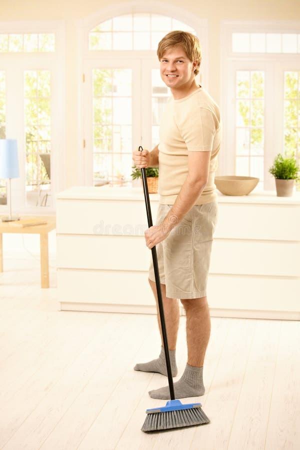 Τύπος που σκουπίζει το πάτωμα στοκ εικόνα με δικαίωμα ελεύθερης χρήσης