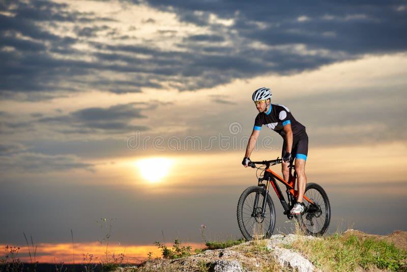 Τύπος στα γυαλιά, το κράνος και sportswear που οδηγούν στο ποδήλατο βουνών στον απότομο βράχο ενάντια στον ουρανό βραδιού στοκ φωτογραφία με δικαίωμα ελεύθερης χρήσης