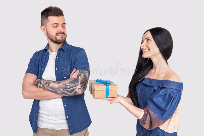 Τύπος Το κορίτσι δίνει ένα δώρο στον τύπο που προσβάλλεται από την ντυμένος στον περιστασιακό ιματισμό στάση μπροστά από έναν γκρ στοκ φωτογραφία με δικαίωμα ελεύθερης χρήσης