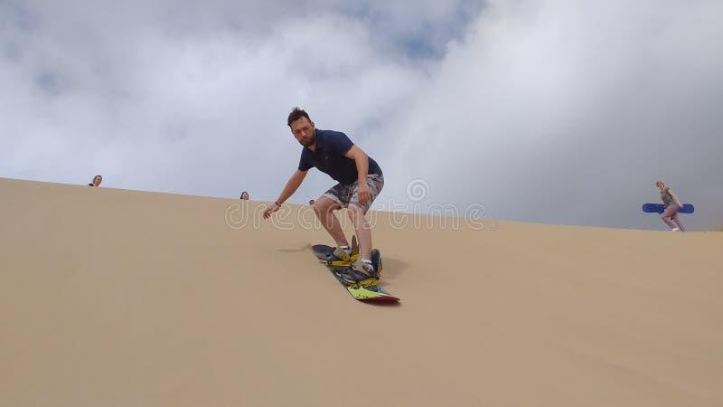 Τύπος Sandboarding στους αμμόλοφους άμμου στοκ εικόνες