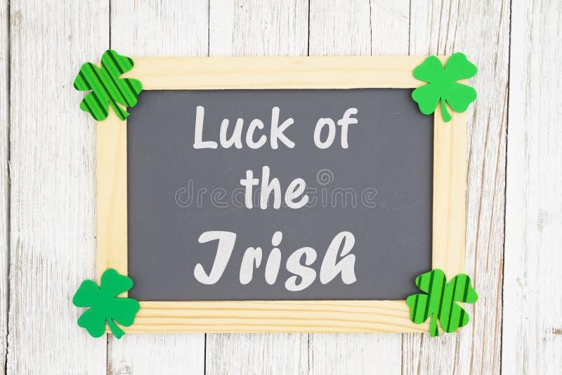 Τύχη του ιρλανδικού κειμένου σε έναν πίνακα κιμωλίας με τα πράσινα τριφύλλια στοκ εικόνες
