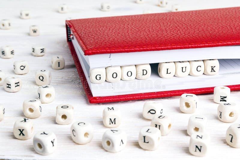 Τύχη Cood φράσης που γράφεται στους ξύλινους φραγμούς στο κόκκινο σημειωματάριο στο whi στοκ φωτογραφία