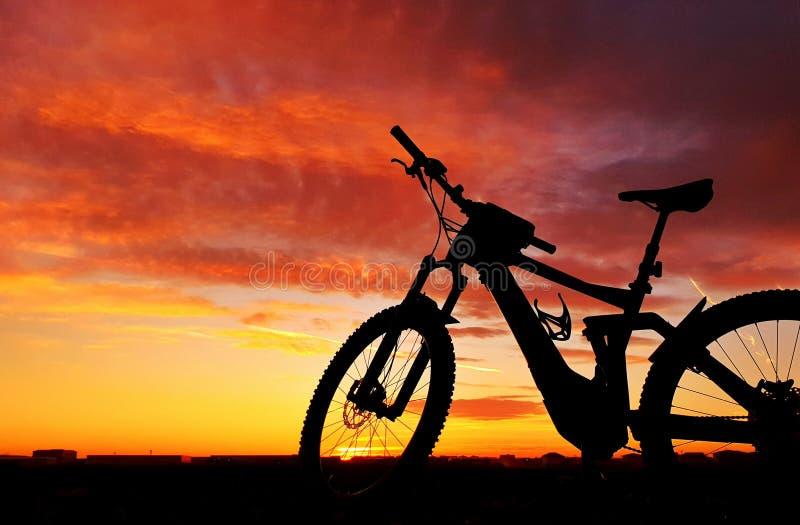 Υβριδικό ηλεκτρικό ποδήλατο με το υπόβαθρο ηλιοβασιλέματος στοκ εικόνα με δικαίωμα ελεύθερης χρήσης