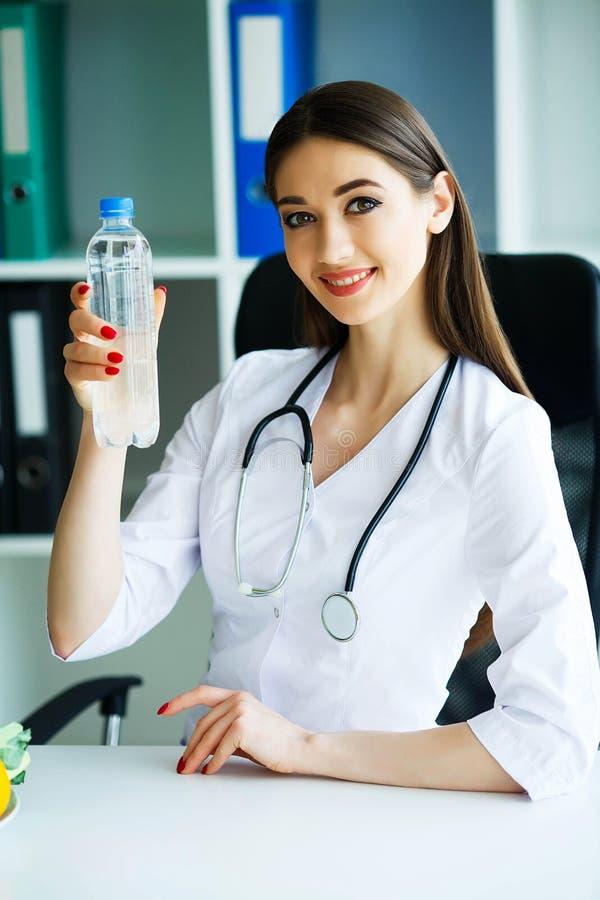 Υγεία και ομορφιά Διαιτολόγος που κρατά ένα μπουκάλι νερό στα χέρια κατανάλωση υγιής Ένας γιατρός με ένα ευτυχές χαμόγελο στοκ φωτογραφίες