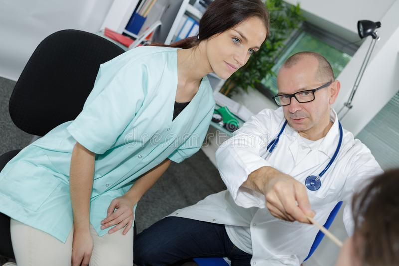 Υγειονομική περίθαλψη και ιατρική έννοια - γιατρός και νοσοκόμα με τον ασθενή στοκ εικόνα