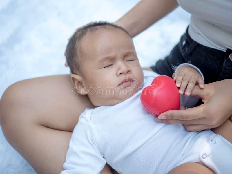 Υγειονομική περίθαλψη και ιατρική αγάπη, νεογέννητο μωρό με την κόκκινη καρδιά στοκ εικόνες
