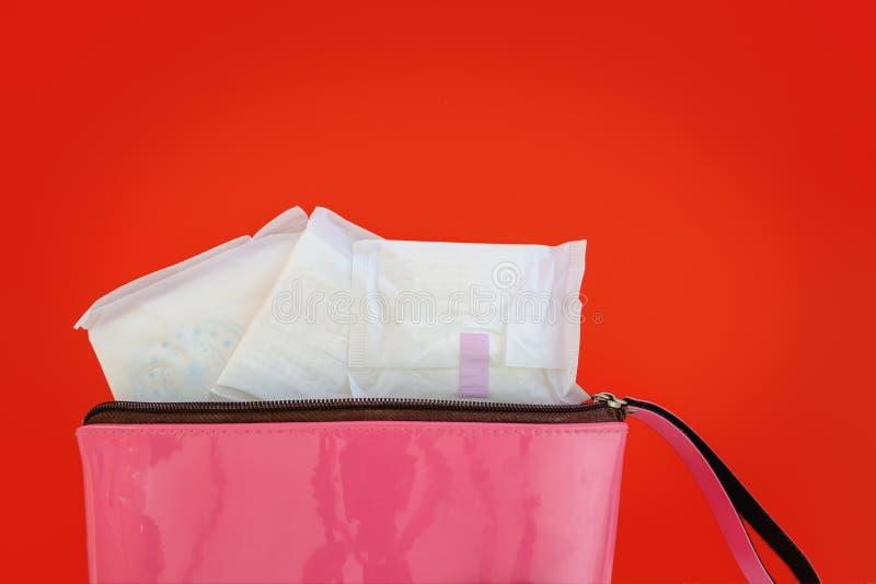 Υγειονομική πετσέτα στη ρόδινη τσάντα γυναικών ` s στο κόκκινο υπόβαθρο στοκ φωτογραφίες με δικαίωμα ελεύθερης χρήσης