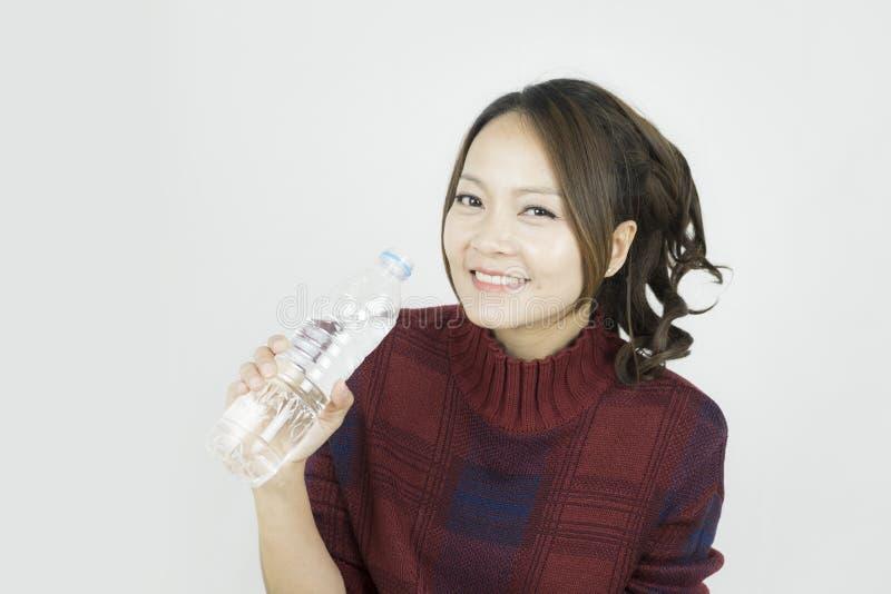Υγιές ασιατικό νέο όμορφο πόσιμο νερό γυναικών στοκ εικόνες