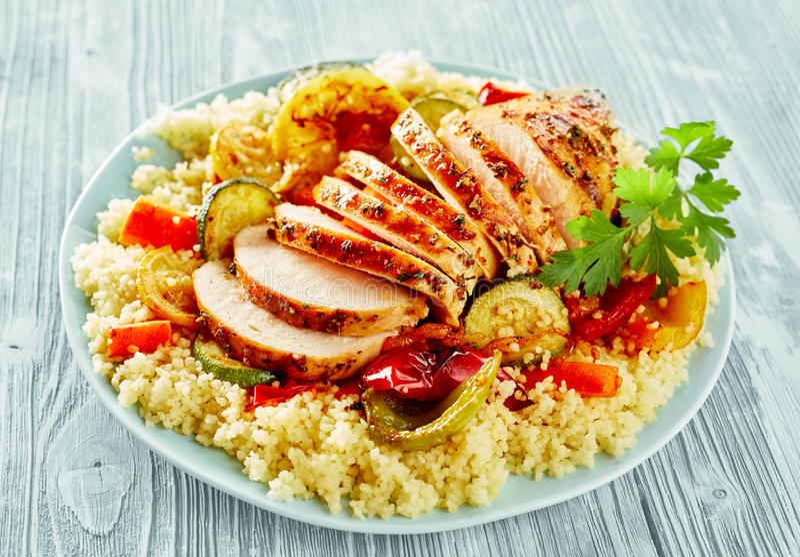 Υγιές αδύνατο ψημένο στη σχάρα στήθος κοτόπουλου στο κουσκούς στοκ εικόνα