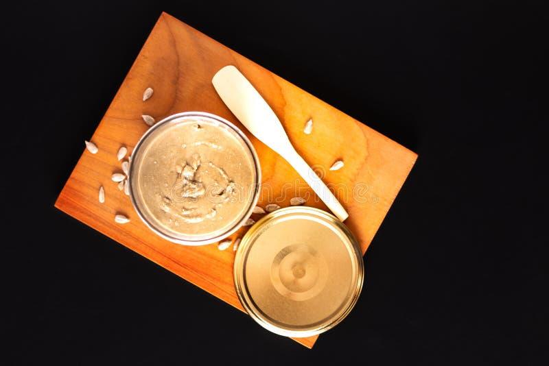 Υγιές βούτυρο ηλίανθων έννοιας τροφίμων homemake στο βάζο γυαλιού από τους οργανικούς σπόρους ηλίανθων στο μαύρο υπόβαθρο στοκ φωτογραφία με δικαίωμα ελεύθερης χρήσης