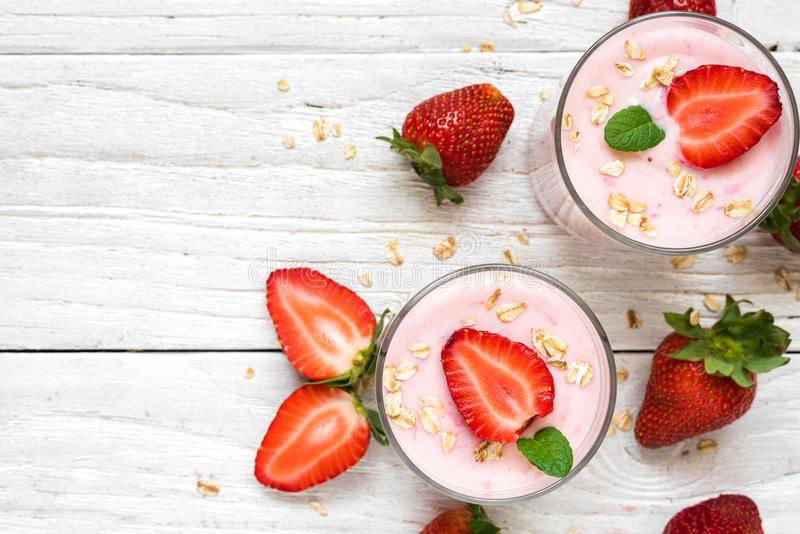 Υγιές γιαούρτι φραουλών με τις βρώμες και μέντα στα γυαλιά με τα φρέσκα μούρα πέρα από τον άσπρο ξύλινο πίνακα στοκ εικόνα