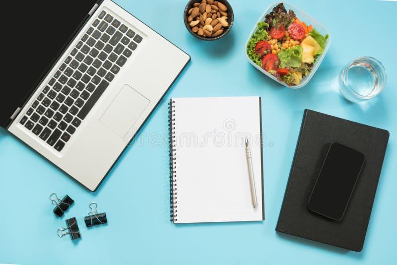 Υγιές επιχειρησιακό μεσημεριανό γεύμα στην αρχή, σαλάτα, αμύγδαλα, νερό στο μπλε Τοπ άποψη με το διάστημα αντιγράφων Κατάλληλη δι στοκ εικόνες