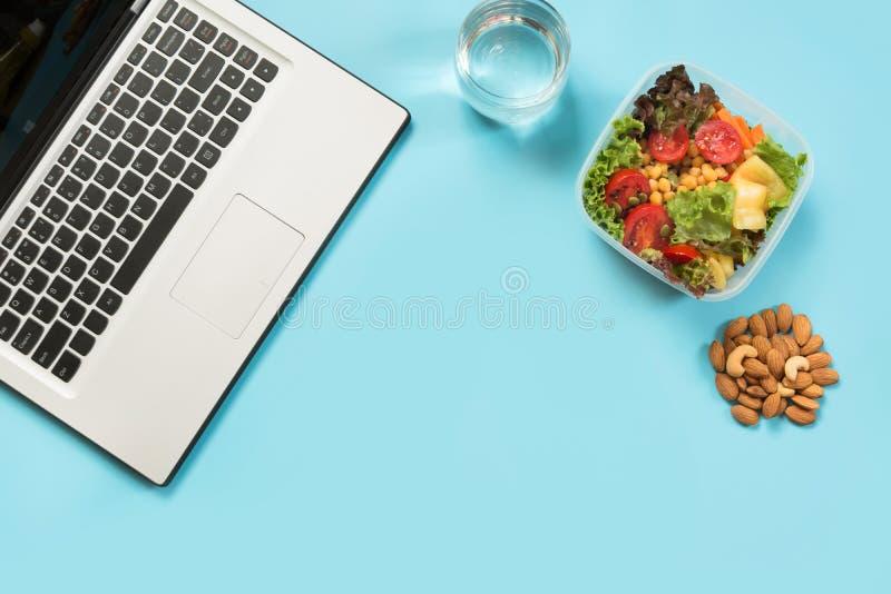 Υγιές επιχειρησιακό μεσημεριανό γεύμα στην αρχή, σαλάτα, αμύγδαλα, νερό στο μπλε Τοπ άποψη με το διάστημα αντιγράφων Υγιής διατρο στοκ φωτογραφίες