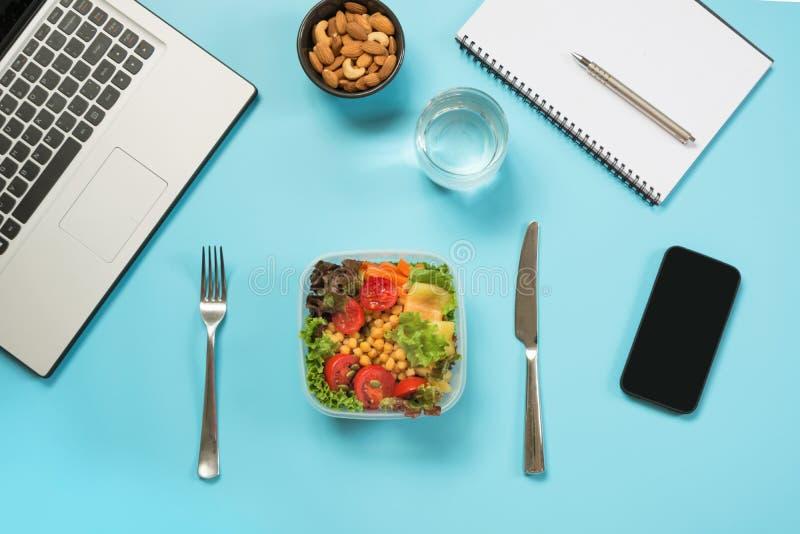 Υγιές επιχειρησιακό μεσημεριανό γεύμα στην αρχή, σαλάτα, αμύγδαλα, νερό στο μπλε Τοπ άποψη με το διάστημα αντιγράφων Υγιής διατρο στοκ φωτογραφία με δικαίωμα ελεύθερης χρήσης