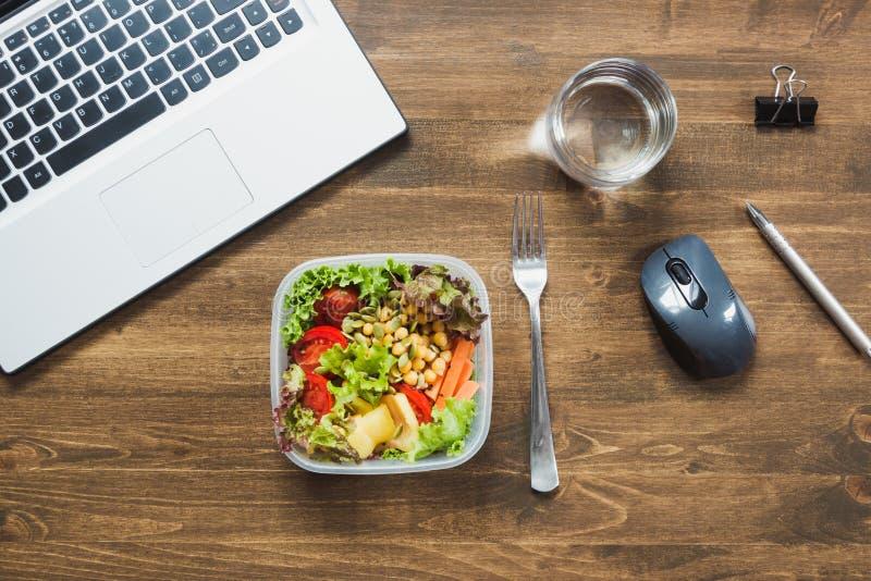 Υγιές επιχειρησιακό μεσημεριανό γεύμα στην αρχή, σαλάτα, νερό στον ξύλινο πίνακα Υγιής διατροφή έννοιας lunchbox στοκ εικόνα με δικαίωμα ελεύθερης χρήσης