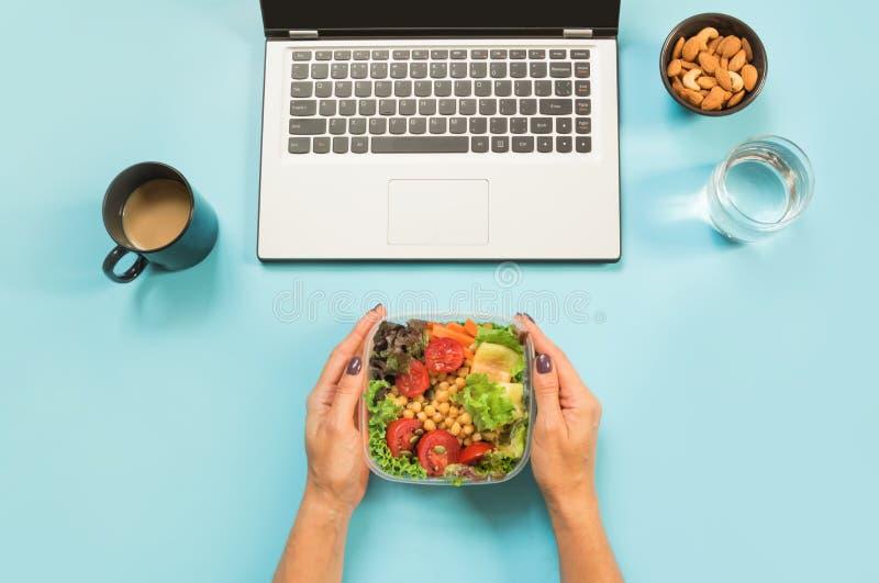 Υγιές επιχειρησιακό μεσημεριανό γεύμα στο γραφείο, σαλάτα για το πρόχειρο φαγητό, ποτήρι του νερού, αμύγδαλα, φλιτζάνι του καφέ σ στοκ φωτογραφίες