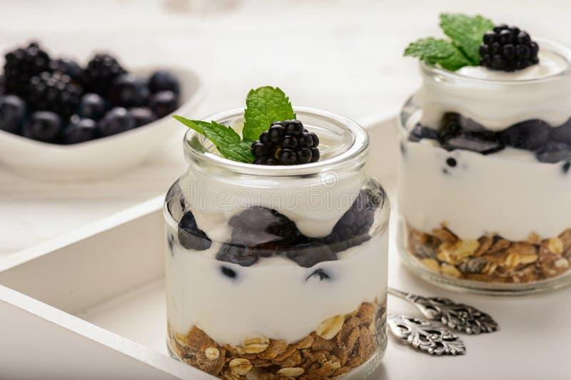 Υγιές επιδόρπιο γιαουρτιού με το muesli, τα βατόμουρα και τα βακκίνια στον άσπρο ξύλινο πίνακα στοκ εικόνες
