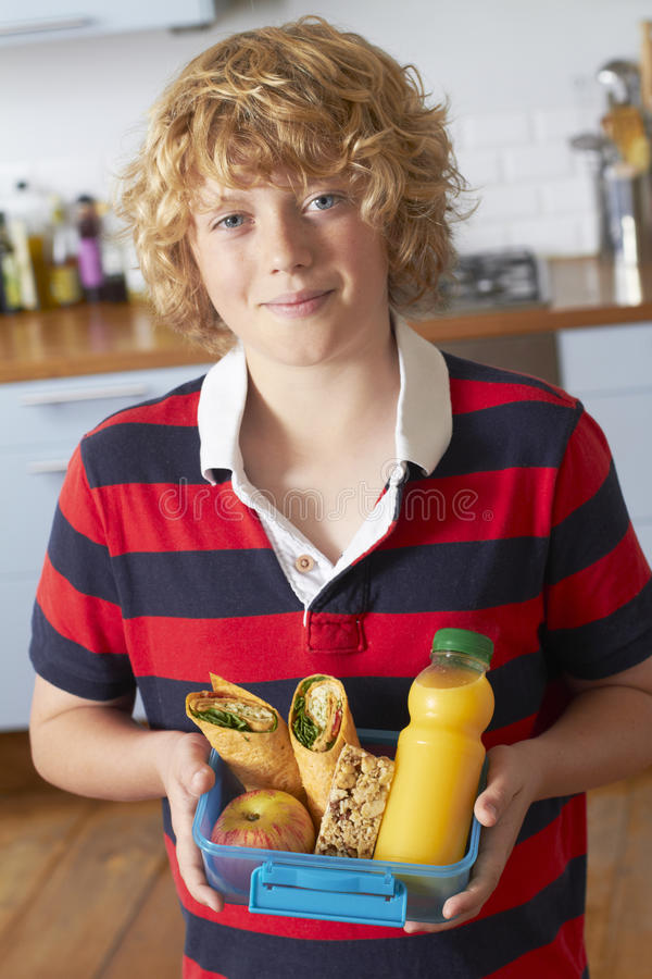 Υγιές καλαθάκι με φαγητό εκμετάλλευσης αγοριών στην κουζίνα στοκ φωτογραφία