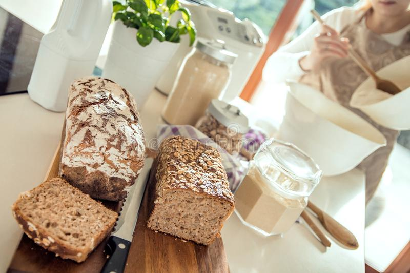 Υγιές κατ' οίκον ψημένο ψωμί που βρίσκεται countertop Η γυναίκα προετοιμάζει το ano στοκ φωτογραφία με δικαίωμα ελεύθερης χρήσης