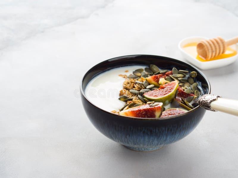 Υγιές κύπελλο γιαουρτιού προγευμάτων με το granola και το σύκο στοκ εικόνες