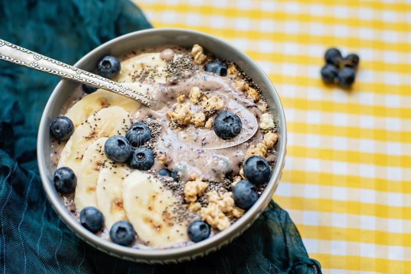 Υγιές κύπελλο καταφερτζήδων μούρων προγευμάτων που ολοκληρώνεται με την μπανάνα, το granola, τα βακκίνια και τους σπόρους chia με στοκ φωτογραφία